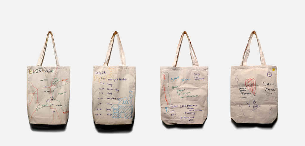 Four white tote bags decorated by group participants.