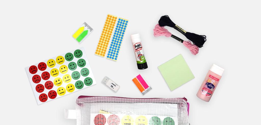 Stationery spread out on a white background, including smiley face stickers with red sad faces, yellow neutral faces, and green happy faces.
