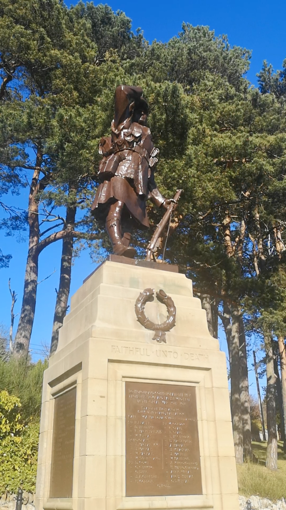 picture of a statue of a kilted soldier from the first world war, sculpted in bronze on top of a cairn