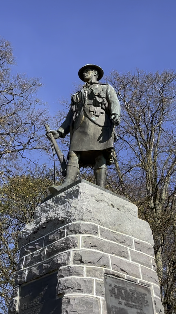 a picture of a statue of a kilted soldier from the first world war, sculpted in bronze on top of a cairn