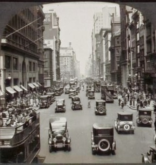 Lots of old ford cars on a busy street