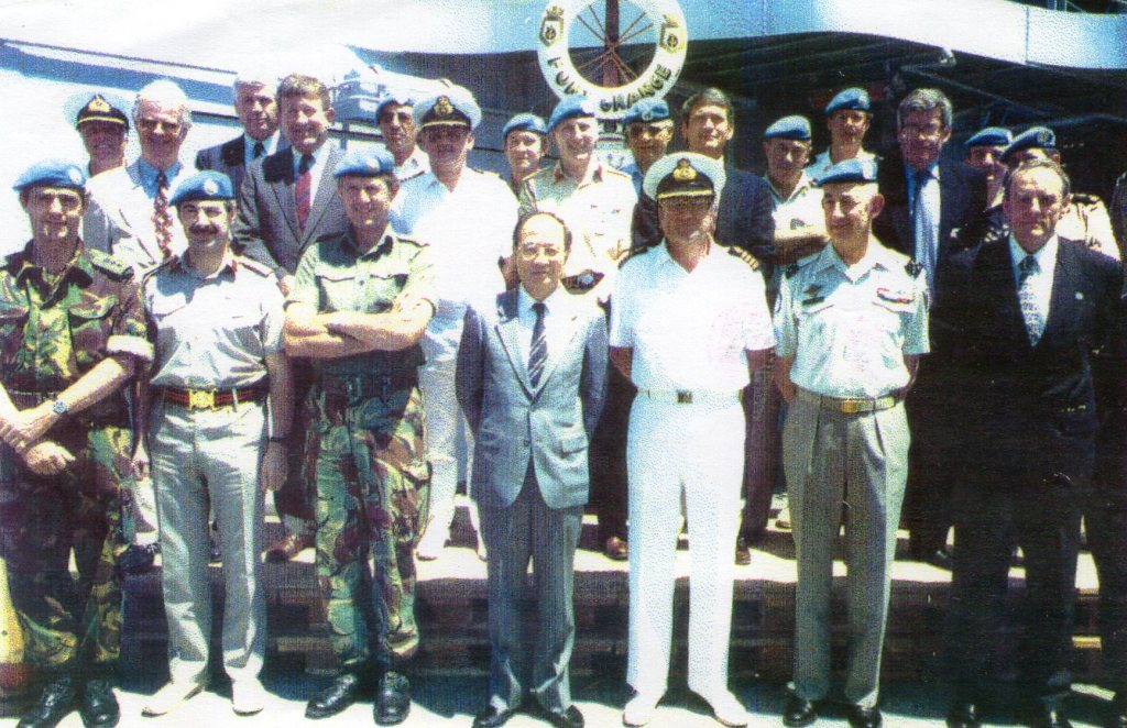 a group of military officers and diplomats wearing UN berets posing for a formal photograph on the deck of a ship