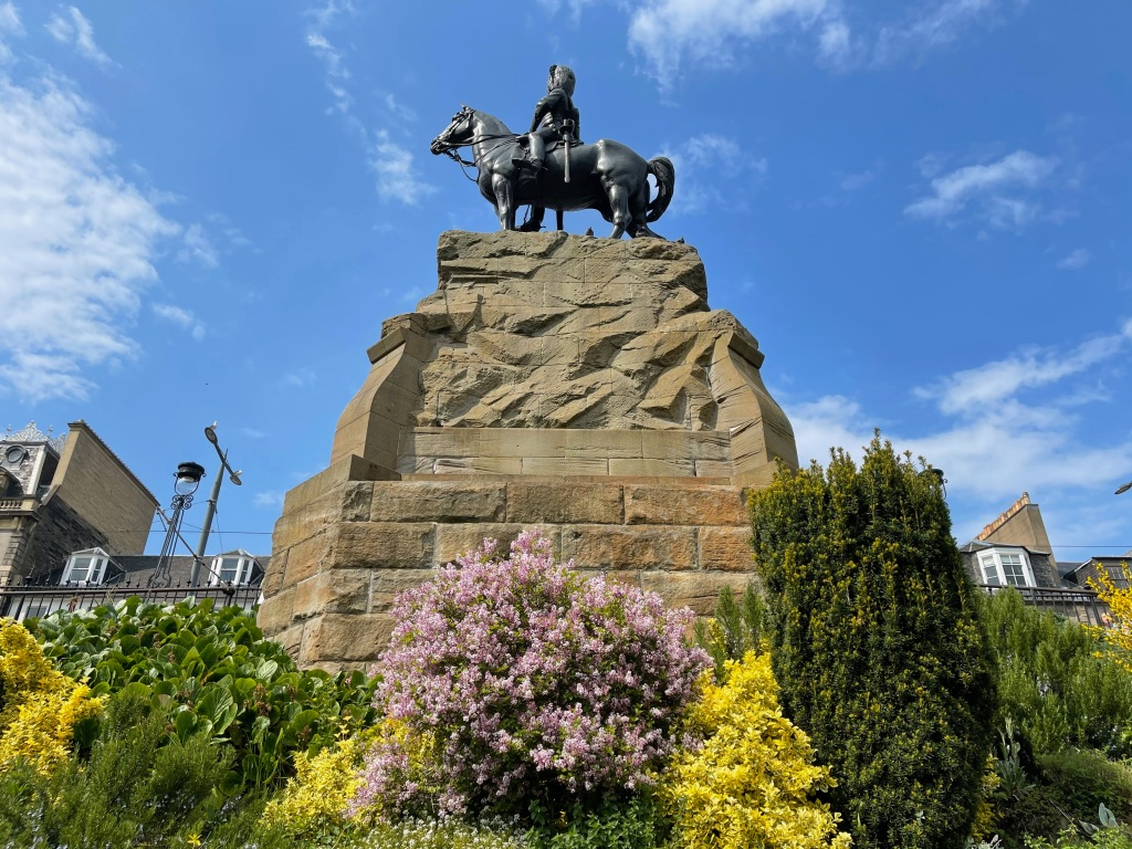 picture of the rear of the Royal Scots Greys Memorial, Princes Street Gardens, Edinburgh, a statue of a soldier on a horse wearing a tall ostrich feather hat